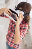 Top view of pre-teen girl opening VR headset front lid. Skilled user. The top view of a petite pre-teen girl wearing a VR headset and opening a front lid of it Stock Image