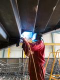Skilled welder. A skilled welder at work ,welding in the overhead position Stock Image