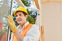 Skilled window fitter mounting window. Installation at woodhouse Royalty Free Stock Image
