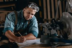 Skilled woodworker drawing new project. Smiling skilled woodworker sitting at table in protective glasses drawing his new project in the workshop Royalty Free Stock Image