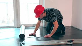 Skilled worker man with red helmet lay sub-flooring mat in new room stock video footage