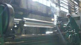 Skilled Worker Operates at Large Powerful Rotating Machine. KAZAN, TATARSTAN/RUSSIA - JUNE 12 2016: Skilled worker in helmet operates at large powerful rotating stock footage