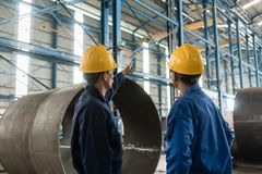 Skilled worker pointing up while giving instructions to an apprentice. In a factory manufacturing boilers Stock Photo