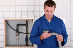 Skilled worker replacing pipe. Skilled worker replacing defective pipe Stock Photo