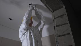 Skilled worker in work wear making drywall ceiling holes for light installation stock footage