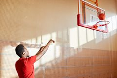 Skilled young basketball player training on court. Serious confident young African-American man throwing ball in basket while playing basketball alone on Royalty Free Stock Photo