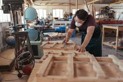 Skilled woodworker sanding furniture in his large workshop. Skilled young carpenter wearing a protective mask and glasses hand sanding pieces of a wooden Royalty Free Stock Photos