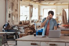 Woodworker using a phone and laptop in his large workshop. Skilled young craftsman standing at a workbench in his large workshop working online with a laptop and Stock Images