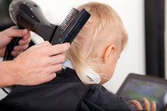 Skilled young hairdresser is setting hair of child Royalty Free Stock Photos
