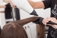 Skilled young hairdresser is using a hairdryer in Royalty Free Stock Images