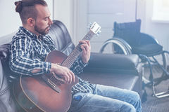 Skilled young handicap playing guitar indoors. Finding new hobby. Bearded skilled talented handicap sitting on the couch next to the wheelchair at home and Stock Photography
