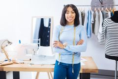 Skilled young worker standing with her arms crossed and smiling. Confident tailor. Young qualified skilled tailor smiling and standing with her arms crossed Stock Image