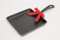 Skillet cuadrado del arrabio con el arco rojo Foto de archivo libre de regalías