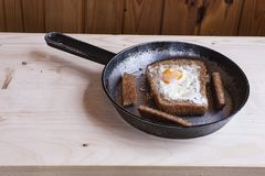 Fried eggs in black bread. Skillet with fried eggs baked in bread Royalty Free Stock Photo