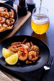 Skillet roasted jumbo shrimp on a black plate. Beer pouring into a glass Stock Photo