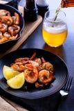 Skillet roasted jumbo shrimp on a black plate. Beer pouring into a glass. Skillet roasted jumbo shrimp on a black plate and beer pouring into a glass Stock Photos