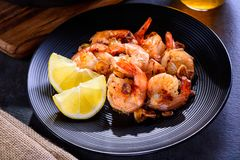 Skillet roasted jumbo shrimp on a black plate. Closeup. Shrimp roasted with sliced garlic and spices Royalty Free Stock Photo
