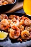 Skillet roasted jumbo shrimp on a black plate. Closeup. Shrimp roasted with sliced garlic and spices Stock Photos