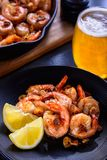 Skillet roasted jumbo shrimp with sliced garlic and spices on a black plate. Closeup. A glass of beer and a skillet in the background Royalty Free Stock Photos