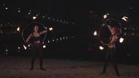 Skillful artists twisting fire hula hoops by hands stock video