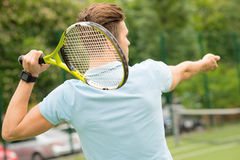 Skillful athlete playing tennis on court. I am ready to beat the ball. Professional tennis player is raising the racket behind his head. Man is holding a ball Royalty Free Stock Photo