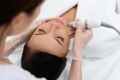Skillful beautician doing facial laser skincare procedure stock photo