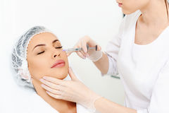 Skillful beautician injecting hyaluronic acid into human face Royalty Free Stock Photos
