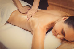 Skillful beautician massaging female body. Serene young woman is lying on massage table and relaxing. Masseuse is pampering her back Royalty Free Stock Photos