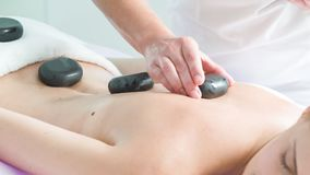 Skillful beautician massaging female body by stones stock video