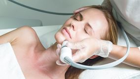 Skillful beautician treating female face by special equipment