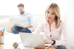 Skillful blond woman using computer for work royalty free stock photo