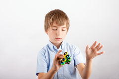 Skillful boy showing fidgeting tricks with four fidget spinners Royalty Free Stock Images
