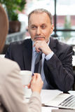 Skillful business partners are discussing project in cafe Stock Photos