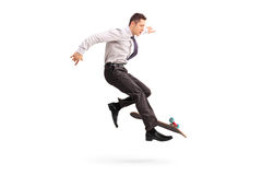 Skillful businessman performing trick on skateboard. Skillful young businessman performing trick on a skateboard isolated on white background Stock Photos