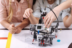 Skillful children testing robot at school. Tech progress. Skilled capable inventive kids sitting at school and enjoying tech class while constructing robot Stock Images