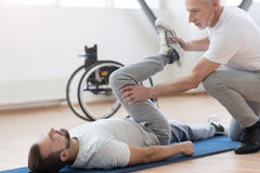 Skillful coach helping the handicapped in the gym. Full of attention. Concentrated skilled masterful orthopedist helping the invalid and providing a Stock Images