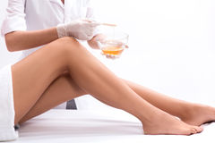 Skillful cosmetologist undergoing waxing procedure royalty free stock image