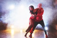 Skillful dancers performing in the dark room under the concert light and smoke. Sensual couple performing an artistic. And emotional contemporary dance Stock Photography