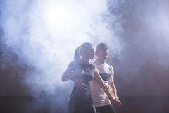 Skillful dancers performing in the dark room under the concert light and smoke. Sensual couple performing an artistic Stock Photo
