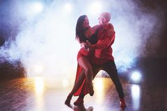 Skillful dancers performing in the dark room under the concert light and smoke. Sensual couple performing an artistic. And emotional contemporary dance Stock Image