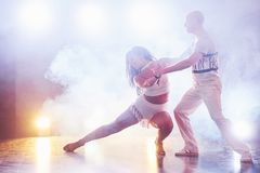 Skillful dancers performing in the dark room under the concert light and smoke. Sensual couple performing an artistic. And emotional contemporary dance Stock Photo