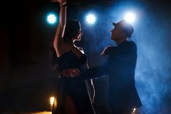 Skillful dancers performing in the dark room under the concert light and smoke. Sensual couple performing an artistic. And emotional contemporary dance Royalty Free Stock Photo