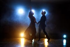 Skillful dancers performing in the dark room under the concert light and smoke. Sensual couple performing an artistic. And emotional contemporary dance Royalty Free Stock Images