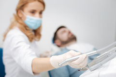 Skillful dentist employing professional equipment. No fear. Capable strong brilliant women taking dental drill for treating her patients caries by filling one of Stock Images