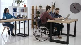 Hipster man in wheelchair working in office stock video