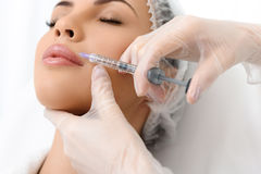 Skillful doctor injecting lips with hyaluronic liquid Stock Image
