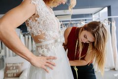 Skillful designer fitting bridal gown to bride. Skillful dress designer fitting wedding gown to women in her boutique. Woman making adjustments to bridal gown in Stock Images