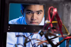 Skillful engineer. Portrait of a young engineer looking at camera through the electronics Stock Photography