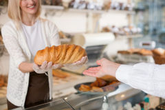 Skillful female baker is serving her customer Royalty Free Stock Photography