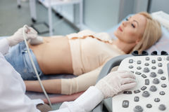 Skillful female obstetrician is doing ultrasonic examination. Close up of arms of gynecologist moving ultrasound transducer on female belly. The pregnant young Stock Photo
